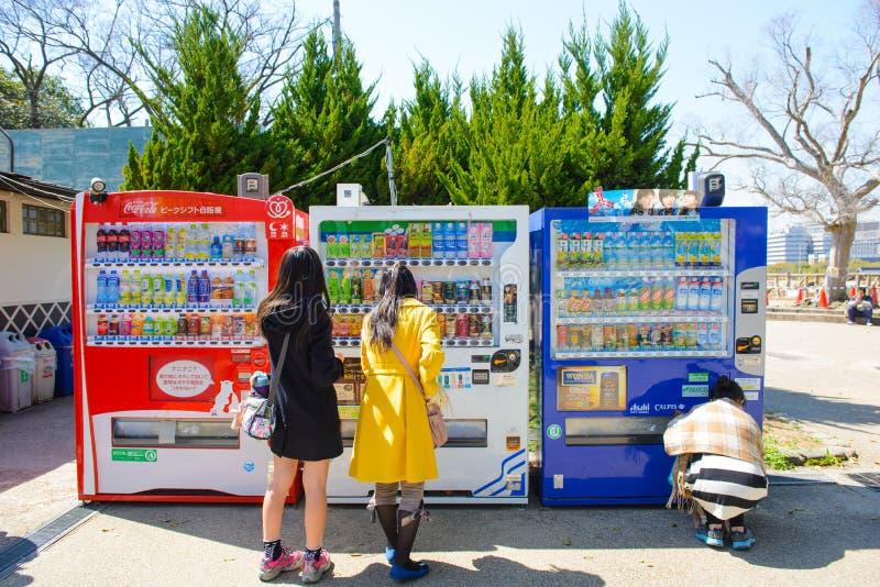 Osaka, Japón - 27 de marzo de 2015: Los turistas son máquina de moneda de la bebida del uso en el castillo de Osaka imagen de archivo libre de regalías