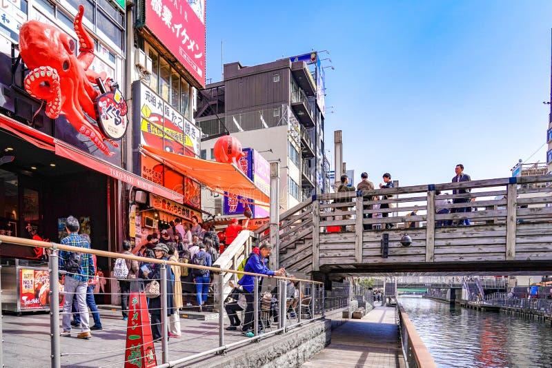 Osaka, Japón - 4 de marzo de 2018 - los turistas y gente local en la línea, esperó para comprar Takoyaki famoso, carne japonesa d imagen de archivo