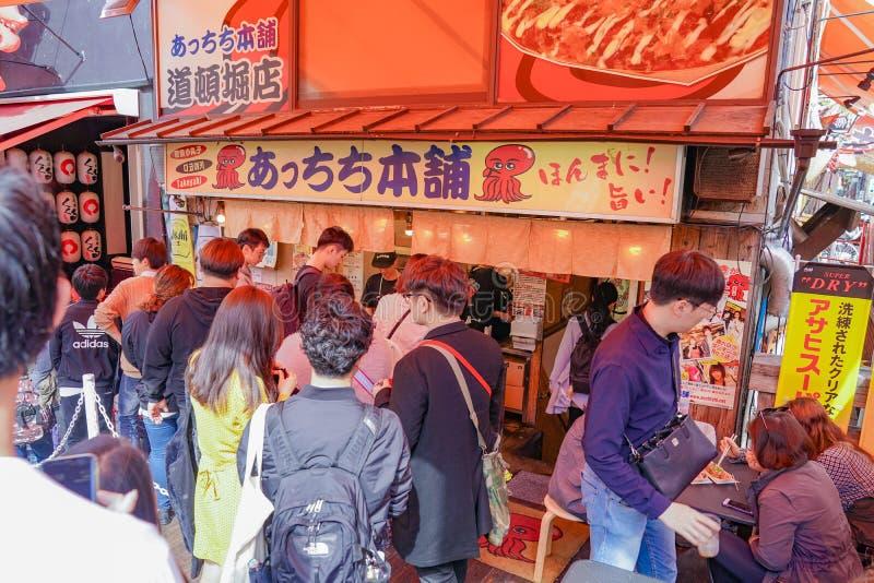 Osaka, Japón - 4 de marzo de 2018 - los turistas y gente local en la línea, esperó para comprar Takoyaki famoso, carne japonesa d fotografía de archivo