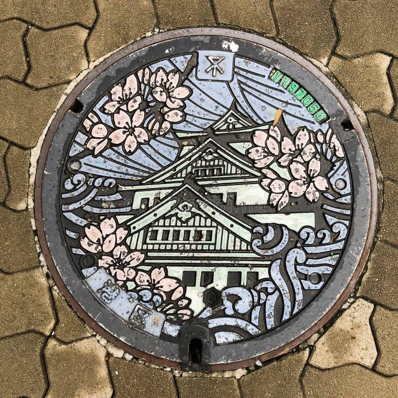 Osaka, Japan: Abwasserkanalkappe/-Kanaldeckel/-luke, japanische Sprachdurchschnitte Osaka lizenzfreies stockbild