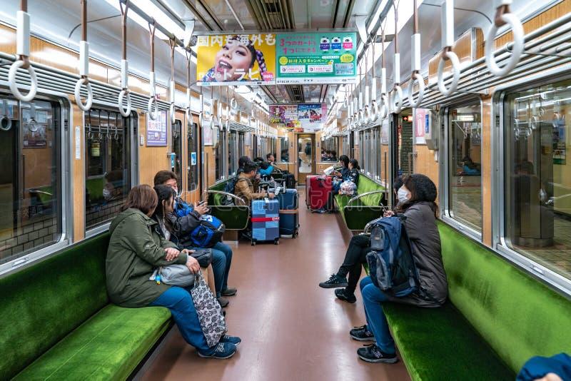 Osaka, Japan - 3 brengen 2018 in de war: De passagiers lopen en zitten in de lokale ondergrondse Trein nr van Japan 8984 en het g royalty-vrije stock foto's