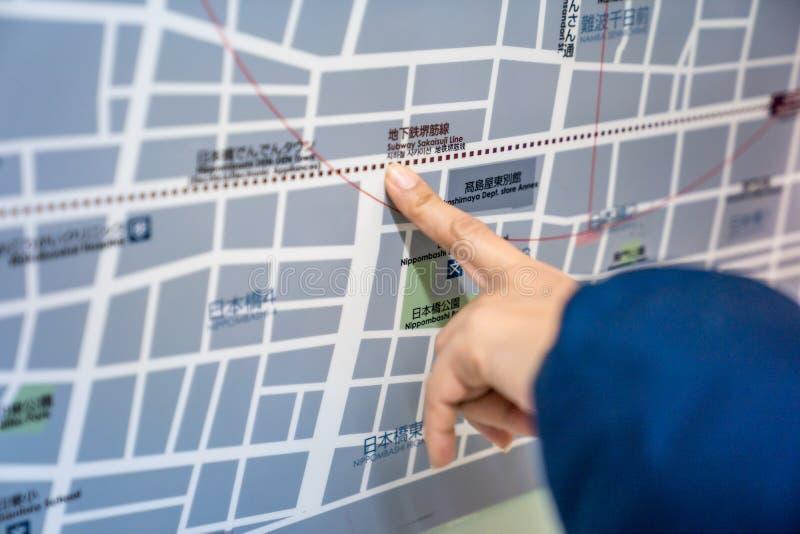 Osaka, Japan - 3 brengen 2018 in de war: De reiziger leest en punt aan de de metrometro van Japan treinkaart op de raad , op het  stock foto's