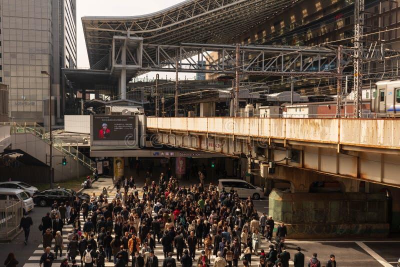 Osaka, Japan - Februari 27, 2019: Massa van mensen in zebrapad die bezig Osaka Station op zonnige dag ingaan stock foto