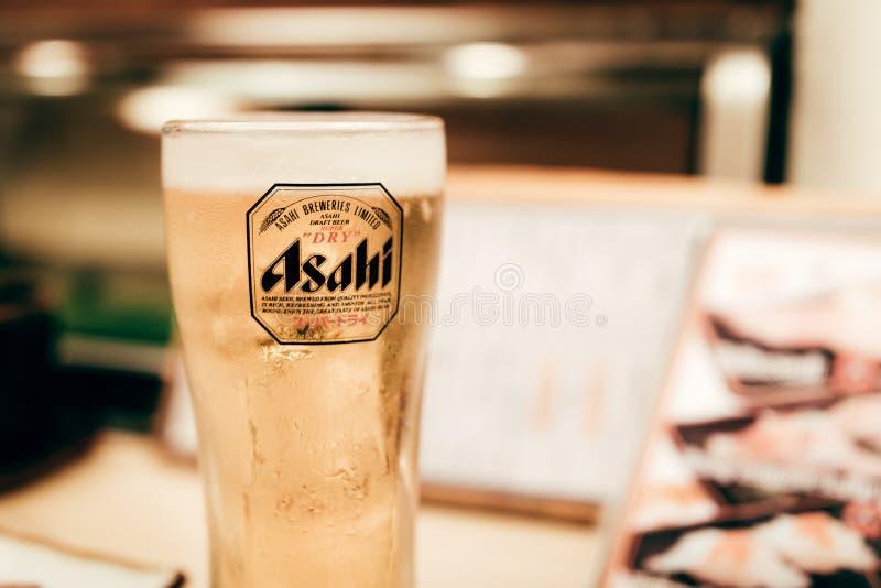 OSAKA JAPAN - Januari 17, 2018: Asahi öl i ett exponeringsglas på trä arkivfoton