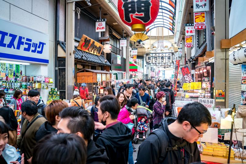 Osaka, Japan - 3 Mar 2018; Japanese local people, tourists and travelers walking and eating at Kuromon Ichiba Market fish market stock image