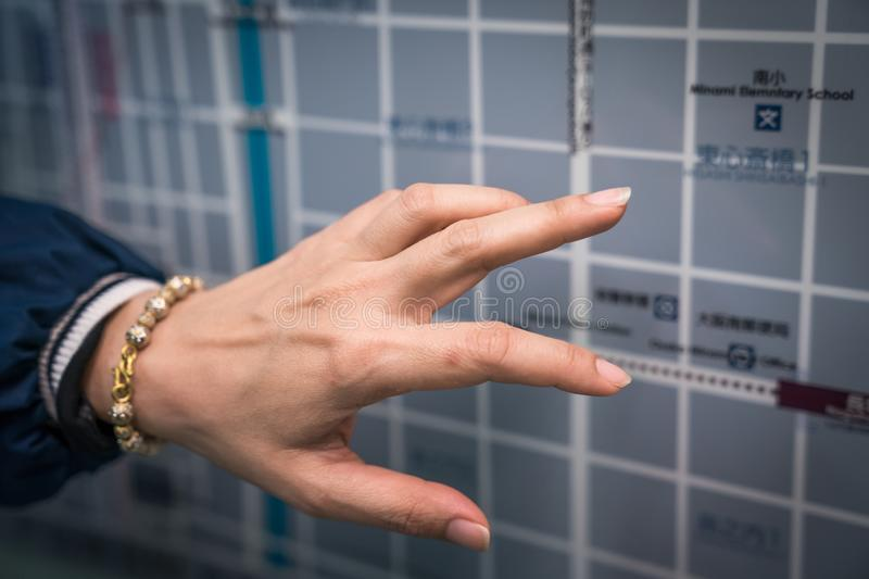 Osaka, Japan - 3 Mar 2018: Traveler reads and point to the Japan`s subway metro train map on the board., in Osaka area, Japan. Osaka, Japan - 3 Mar 2018 stock photography