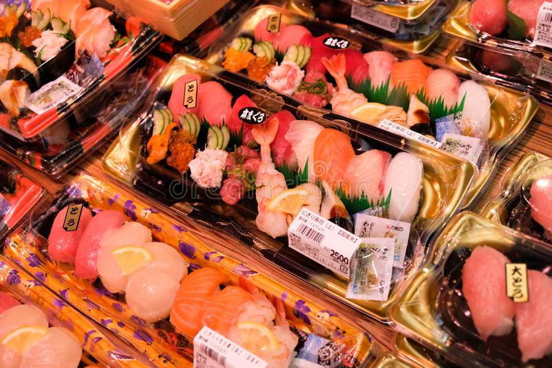Beautiful decorated assorted raw fish sushi. Osaka, Japan - March 19 2019: Beautiful decorated assorted raw fish sushi packed in a box containing tuna, salmon royalty free stock images