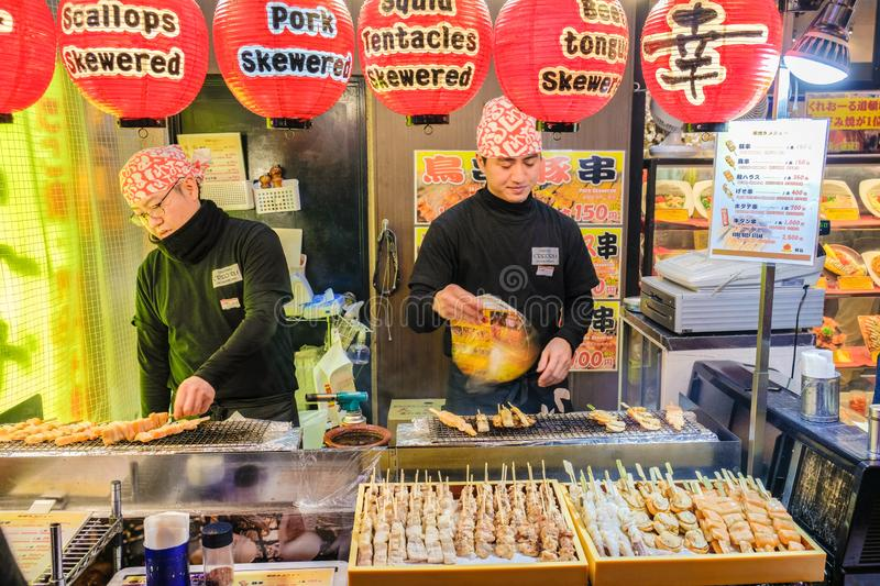 Japanese street food stall vendor cooking and selling seafood meat skewer royalty free stock photography