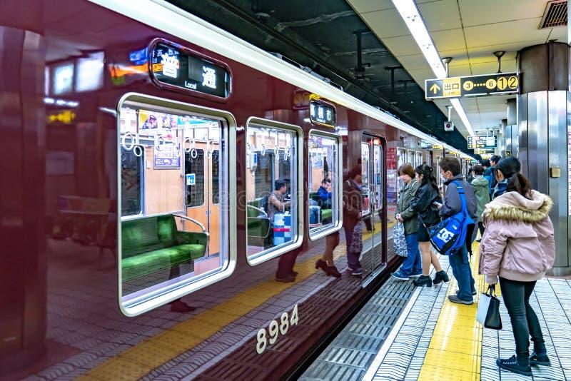 Osaka Japan - 3 Mars 2018: Passagerare går och sitter i det lokala tunnelbanaJapan drevet inte 8984 och gå till det nästa drevet royaltyfri foto
