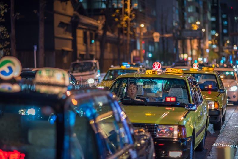 OSAKA JAPAN - November, 17, 2014: Taxitaxiar i nattgatan royaltyfri fotografi
