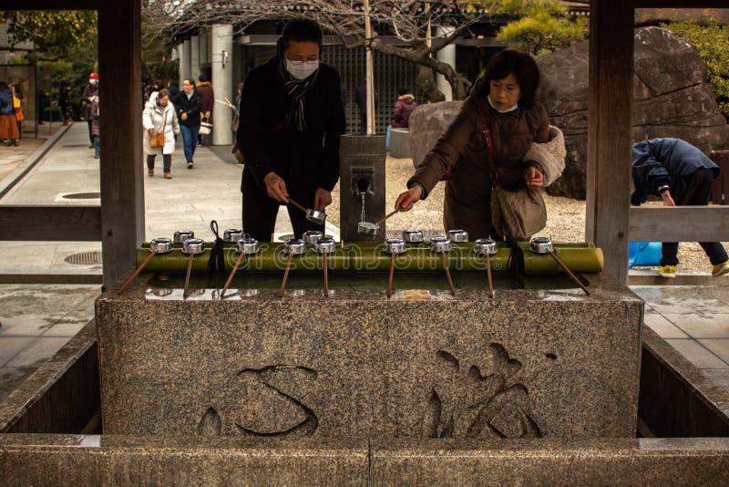 OSAKA, JAPON - 29 JANVIER 2018 : Peuple japonais faisant le rite de purification d'eau de Chozuya dans le temple d'Osaka images libres de droits