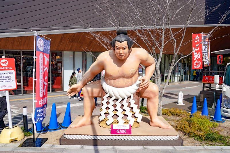 Osaka, Japon - 4 mars 2018 - statue de sumo près du camion traditionnel de nourriture du Japon la table et la chaise sont autour  photos stock