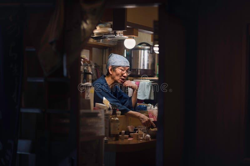 Osaka - 2 novembre 2018 : Personnel dans un petit restaurant d'Izakaya un bar japonais traditionnel pour l'après-travail buvant à photos libres de droits