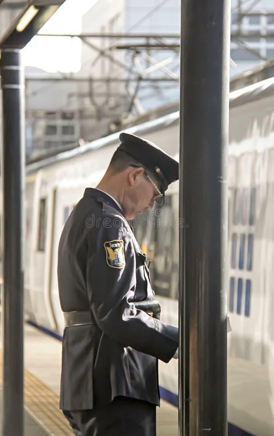 Osaka - 2010: Opinião lateral um oficial japonês em um estação de caminhos de ferro imagem de stock