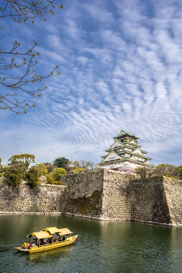Osaka-Schloss und ein touristisches Boot im Stadtburggraben stockfotografie