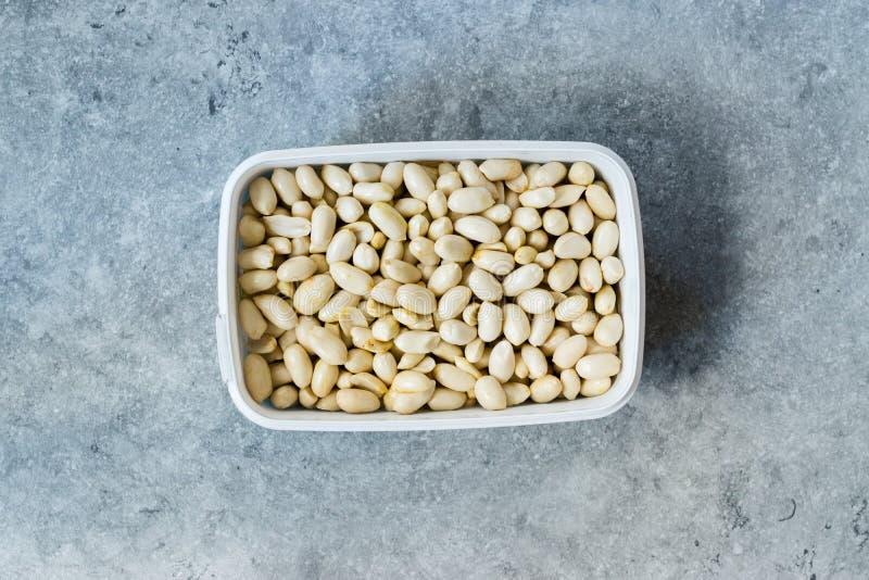 Osaltade, vita skalade råa jordnötter i plastbehållare/förpackning arkivbilder