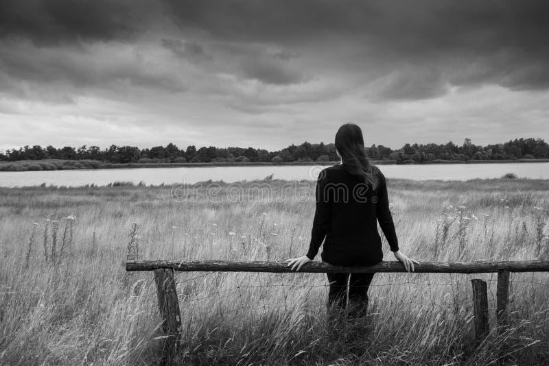 Osamotneni potomstwa deprymowali smutnego kobiety obsiadanie na drewnianego promienia lub ogrodzenia glazurowaniu w odległość mon fotografia stock