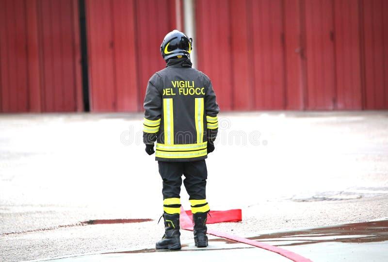Osamotneni Włoscy strażacy z czerwonym pożarniczym wężem elastycznym obraz royalty free