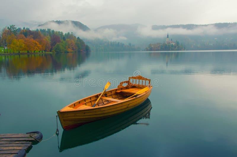 Osamotniona łódź na wodnej powierzchni Krwawić jezioro, Slovenia zdjęcia royalty free