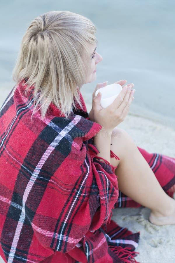 Osamotniona blond kobieta na plaży z filiżanką gorący napój, ciepła czerwona szkocka krata obrazy stock