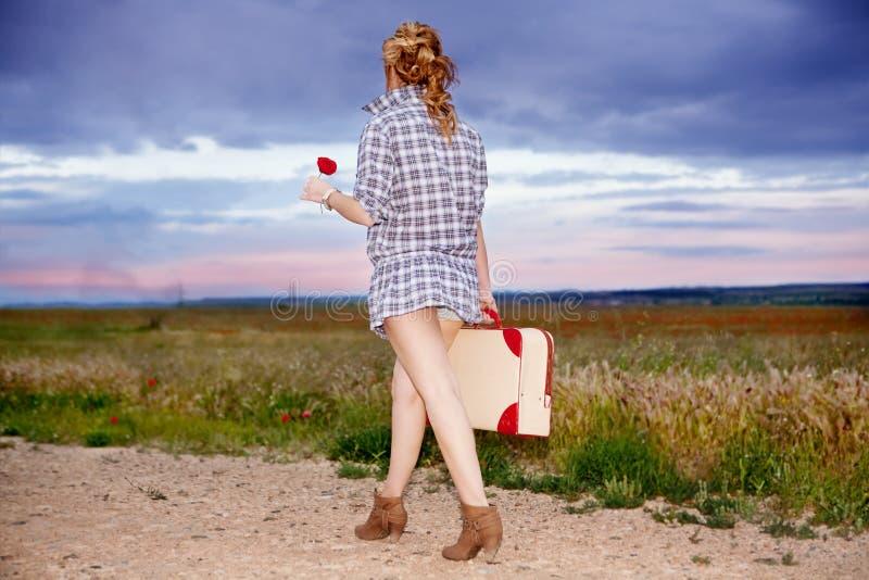 Osamotniona dziewczyna z walizką outdoors i kwiatem. Tra zdjęcia stock