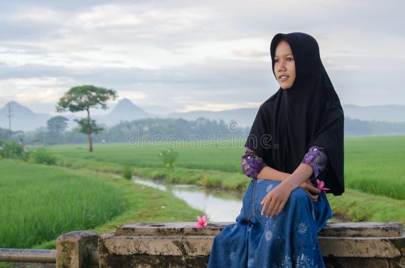 Osamotniona hijab dziewczyna z jej uśmiechem w polu i rzece obraz royalty free