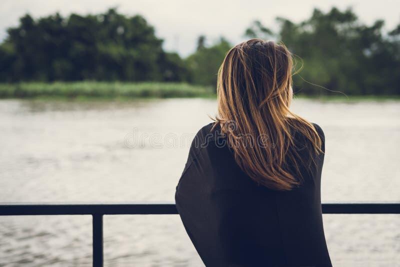 Osamotniona kobieta patrzeje rzekę zdjęcie stock