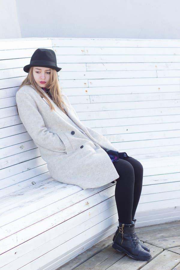 Osamotniona smutna piękna dziewczyna w żakiecie siedzi na białej ławki zimy zimnym słonecznym dniu czarnym kapeluszu i, obrazy royalty free