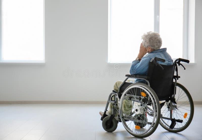 Osamotniona starsza kobieta w wózku inwalidzkim indoors zdjęcia royalty free