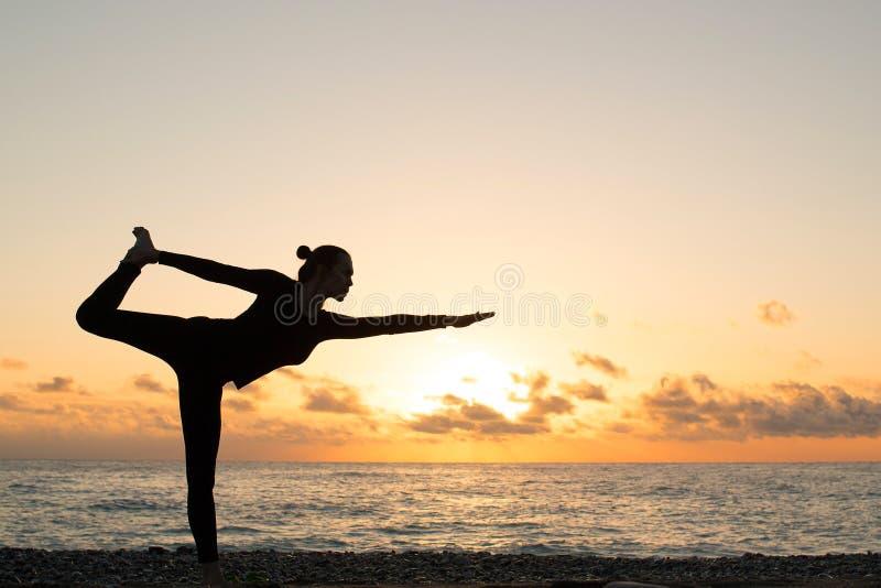 Osamotniona sylwetka kobiety ćwiczy joga na plaży przy zmierzchem zdjęcia royalty free