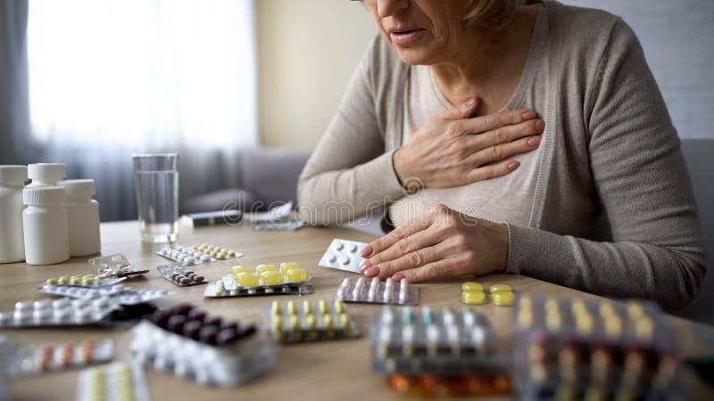 Osamotnionego starej kobiety cierpienia kierowy problem, czuć cierpiący, patrzeje dla pigułek zdjęcie royalty free