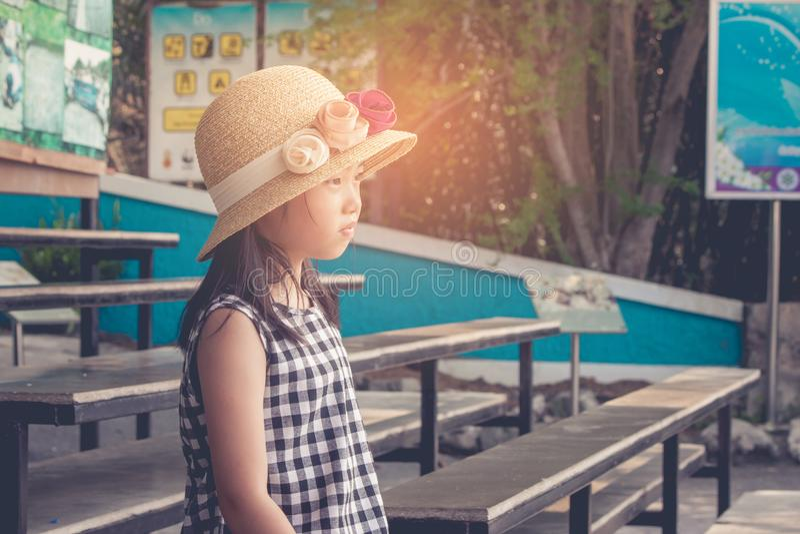 Osamotniony Azjatycki śliczny dzieci być ubranym wyplata kapelusz i obsiadanie na drewnianym długim krześle, ona patrzeje naprzód zdjęcie royalty free