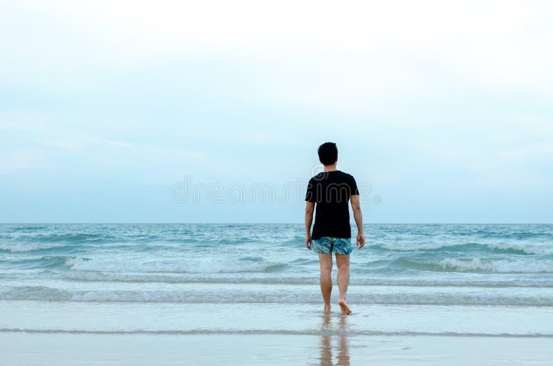 Osamotniony Azjatycki m??czyzna chodzi samotnie na pla?y zdjęcia stock
