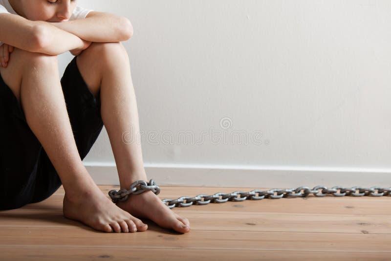 Osamotniony chłopiec obsiadanie w pokoju z łańcuchem na stopie obraz royalty free