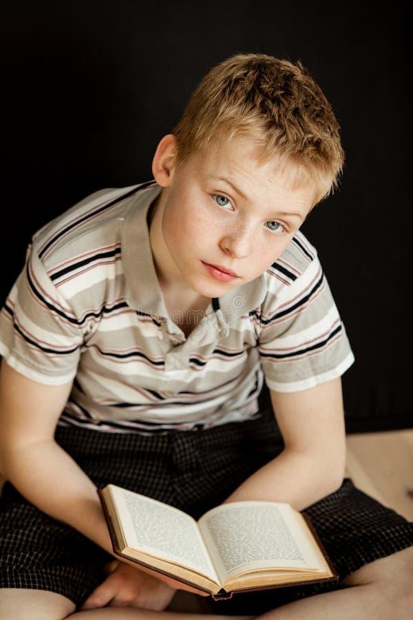 Osamotniony dziecka obsiadanie, czytanie i książka fotografia royalty free