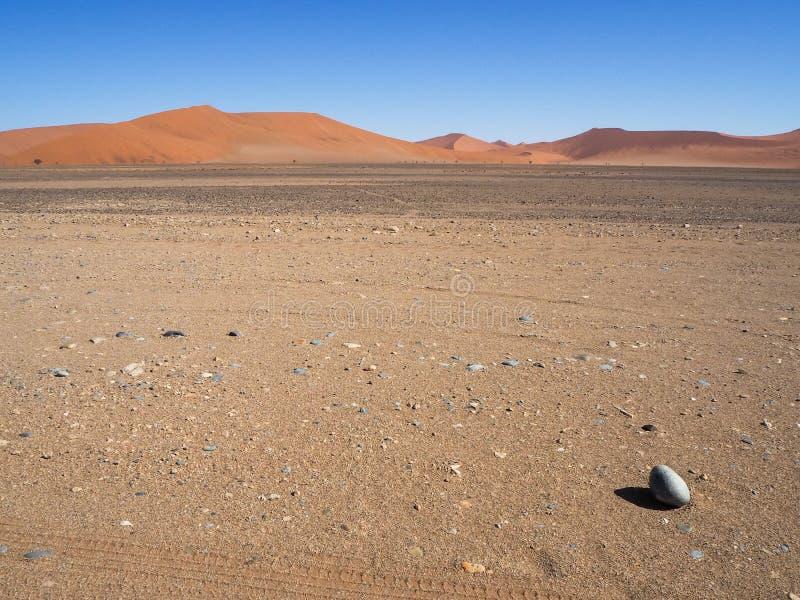 Osamotniony jajeczny kształt skały kamień i cień na szerokim opróżniamy wysuszonego pustynia krajobraz z naturalną piasek diuny w zdjęcie stock