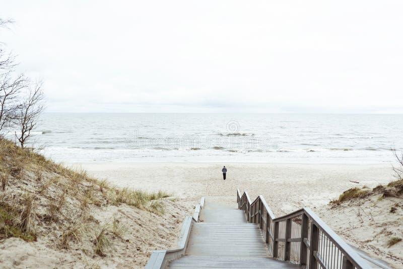 Osamotniony mężczyzna chodzi na plaży wzdłuż linii brzegowej, mora, fotografia stock