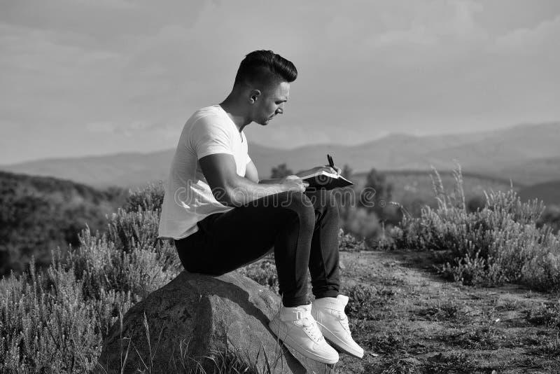 Osamotniony mężczyzna pisze liście jego ukochany Zadumany mięśniowy mężczyzna z książkowy plenerowym zdjęcie royalty free
