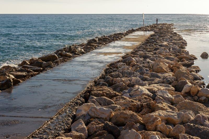 Osamotniony mężczyzna połów na skałach zdjęcie royalty free