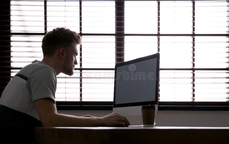 Osamotniony mężczyzny obsiadanie przy komputerem z pustym ekranem obraz royalty free