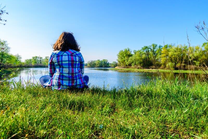 Osamotniony młodej kobiety obsiadanie na banku rzeka zdjęcie stock