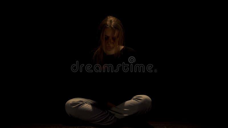 Osamotniony nadużywający żeński obsiadanie w ciemności, nędzna ofiara przemoc domowa zdjęcia stock