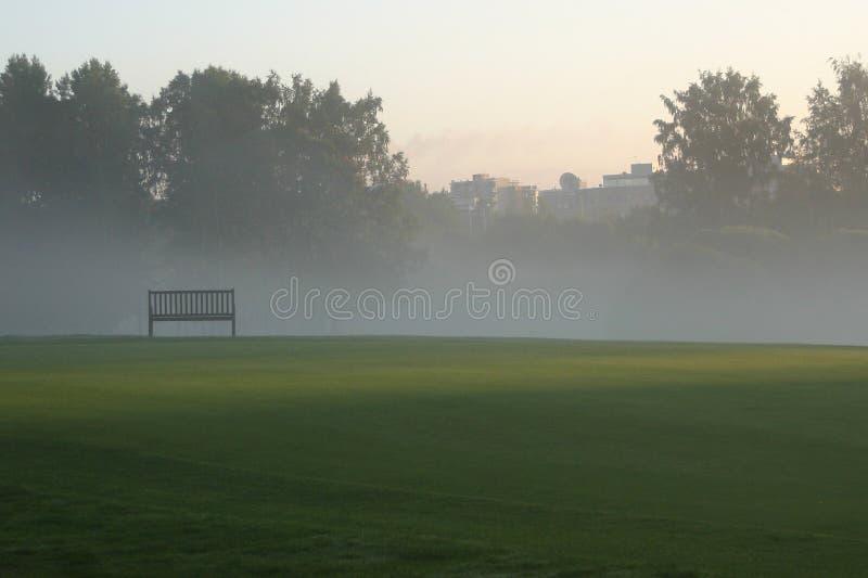 Osamotniony opróżnia ławkę w parku na mglistym ranku fotografia stock