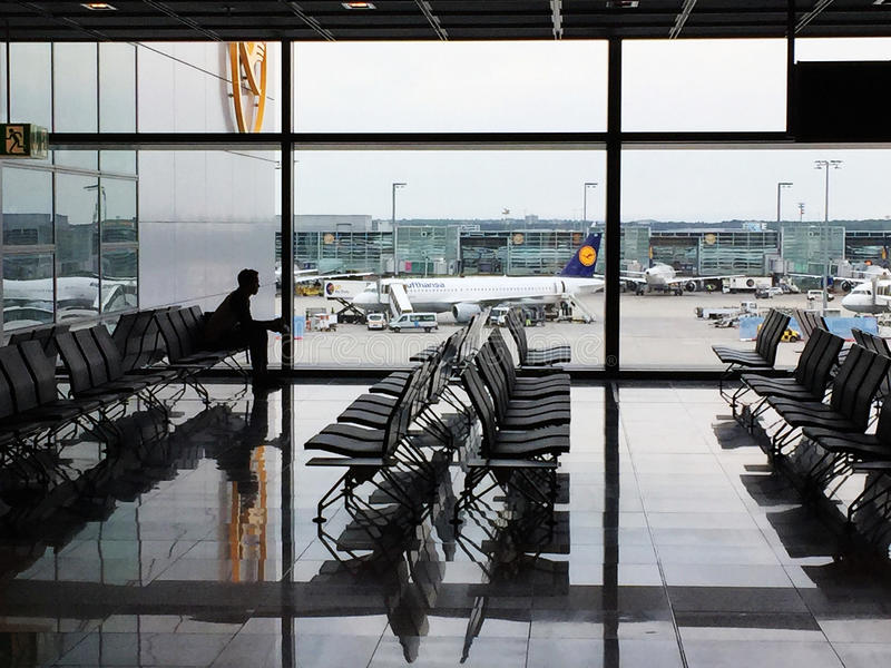 Osamotniony pasażer widzieć w sylwetki czekaniu w Frankfurt lotnisku fotografia royalty free