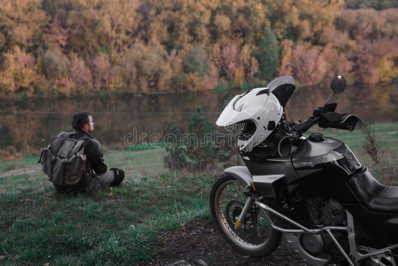Osamotniony poj?cie, m??czyzna siedzi samotnie i spojrzenie przy odleg?o?ci? Przygoda motocykl, motocyklista, A motocyklu kierowc zdjęcie royalty free