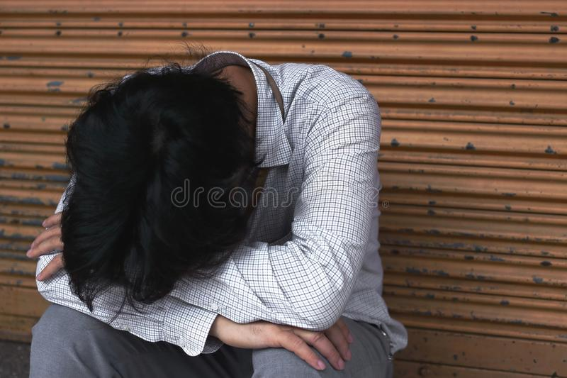Osamotniony przygnębiony Azjatycki mężczyzna siedzi jego kolano na podłoga i ściska zdjęcie royalty free