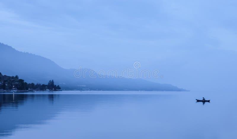 Osamotniony rybak w mgłowych górach, Jeziorny Toba zdjęcie stock