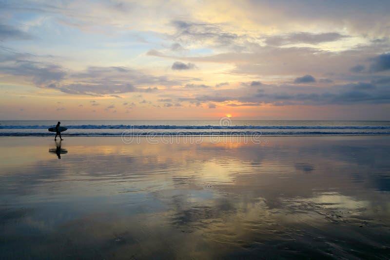 Osamotniony surfingowa odprowadzenie wzdłuż pustej Kuta plaży z zmierzchu niebem obraz stock
