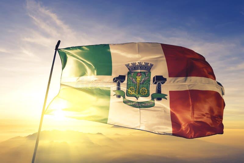 Osasco of Brazil flag waving on the top sunrise mist fog. Osasco of Brazil flag textile cloth fabric waving on the top sunrise mist fog royalty free stock photos