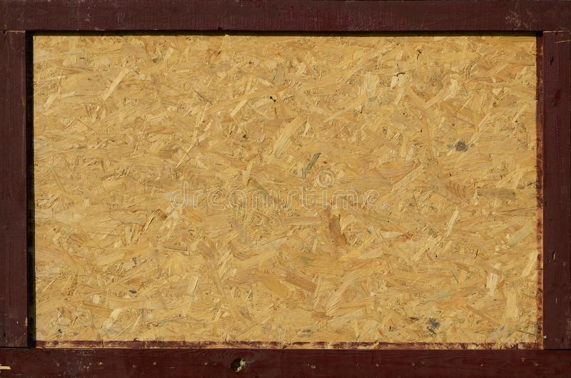 OSB boards are made of brown wood chips sanded into a wooden background stock photography